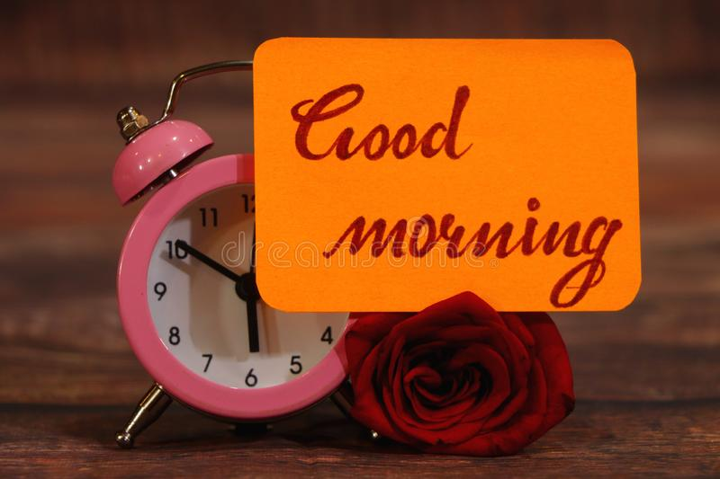 Good Morning text with red rose and alarm clock. royalty free stock photo