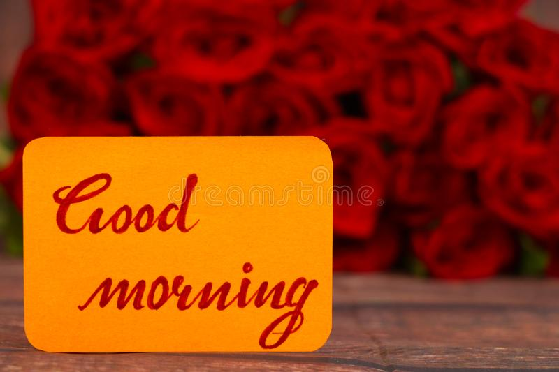 Good Morning text with Red roses in a bunch as a background. stock image