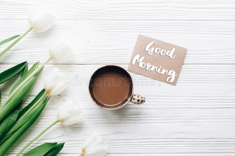 Good morning text sign on greeting card at tulips with coffee on stock image