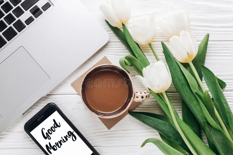 Good morning text sign on phone screen and laptop with morning c royalty free stock images
