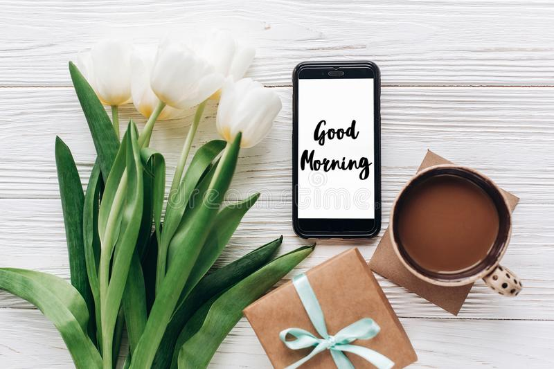 Good morning text sign on phone screen and stylish gift and tulips and coffee on white wooden rustic background. flat lay with fl. Owers and gadget, space for stock photo