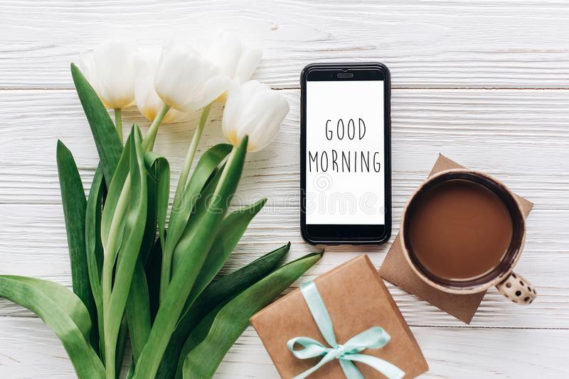 Good morning text sign on phone screen and stylish gift and tulips and coffee on white wooden rustic background. flat lay with fl. Owers and gadget with space royalty free stock photos