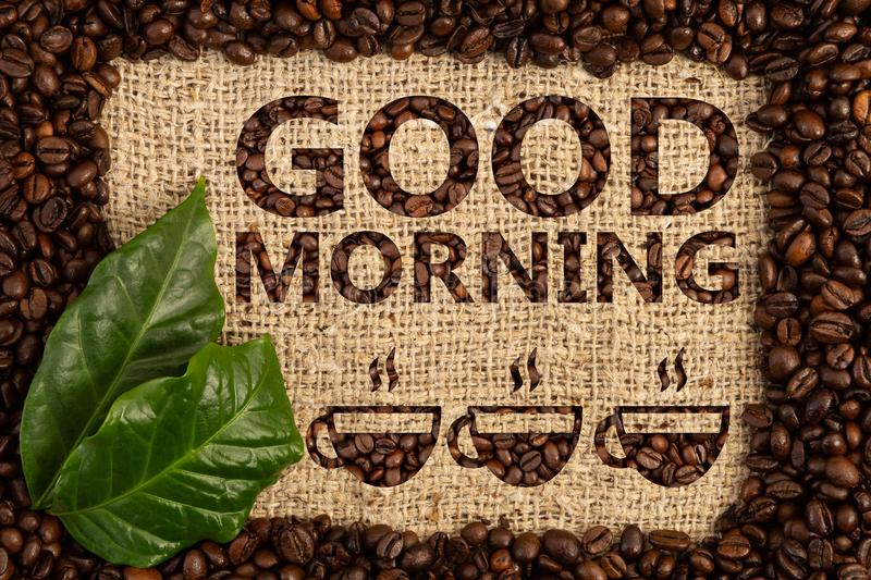 Good morning text with three coffee cups. Good morning text written on burlap textured background with a drawing of three coffee cups under in roasted beans stock images