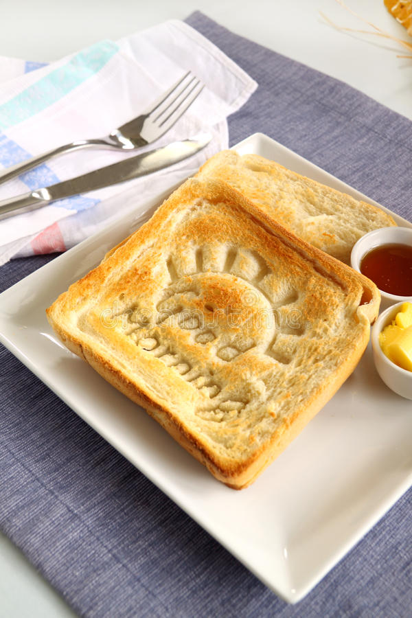 Good Morning Toast. Slice of toast with Good Morning carved into it with butter and honey stock photo