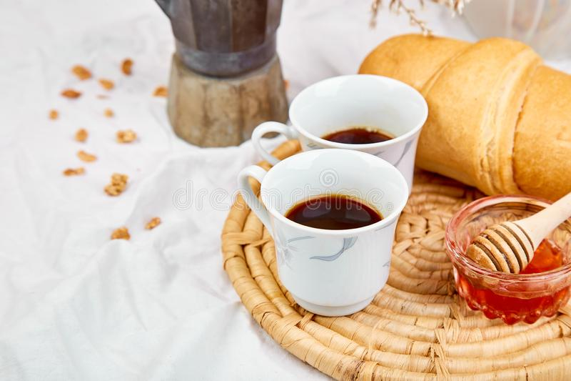 Good morning. Two cup of coffee with croissant and jam. Breakfast on white bed sheets from above. Top view. Flat lay. Copy space. Romantic breakfast royalty free stock photo