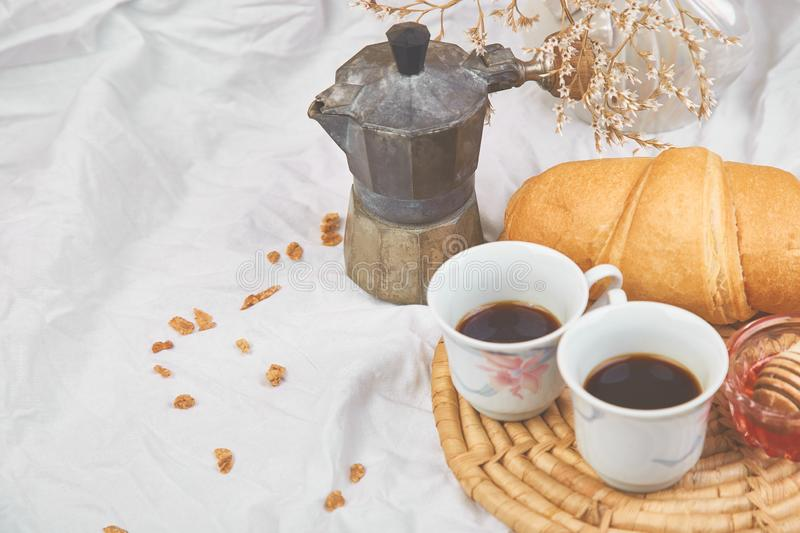 Good morning. Two cup of coffee with croissant and jam. Breakfast on white bed sheets from above. Top view. Flat lay. Copy space. Romantic breakfast royalty free stock photography