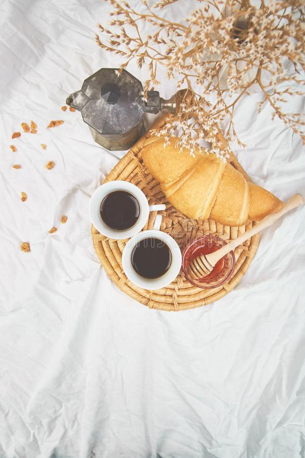 Good morning. Two cup of coffee with croissant and jam. Breakfast on white bed sheets from above. Top view. Flat lay. Copy space. Romantic breakfast royalty free stock image