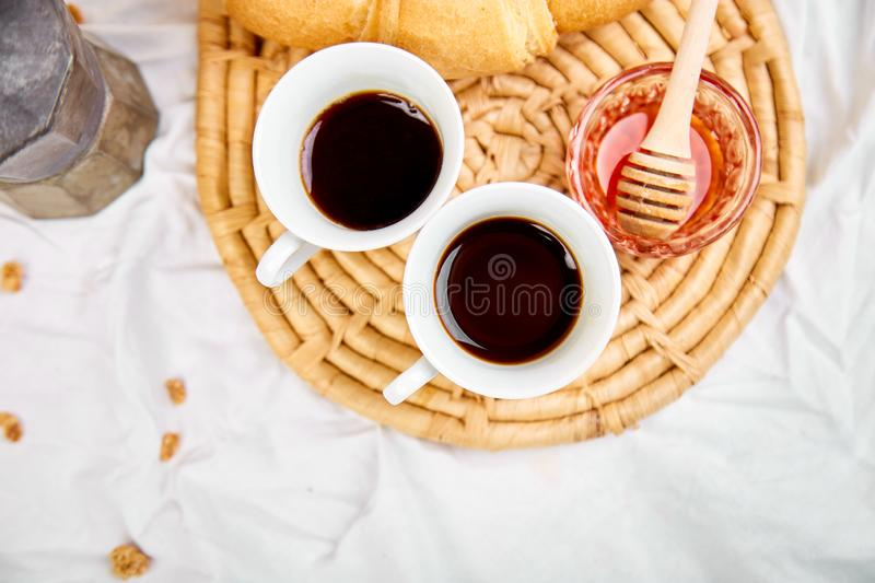 Good morning. Two cup of coffee with croissant and jam. Breakfast on white bed sheets from above. Top view. Flat lay. Copy space. Romantic breakfast stock image
