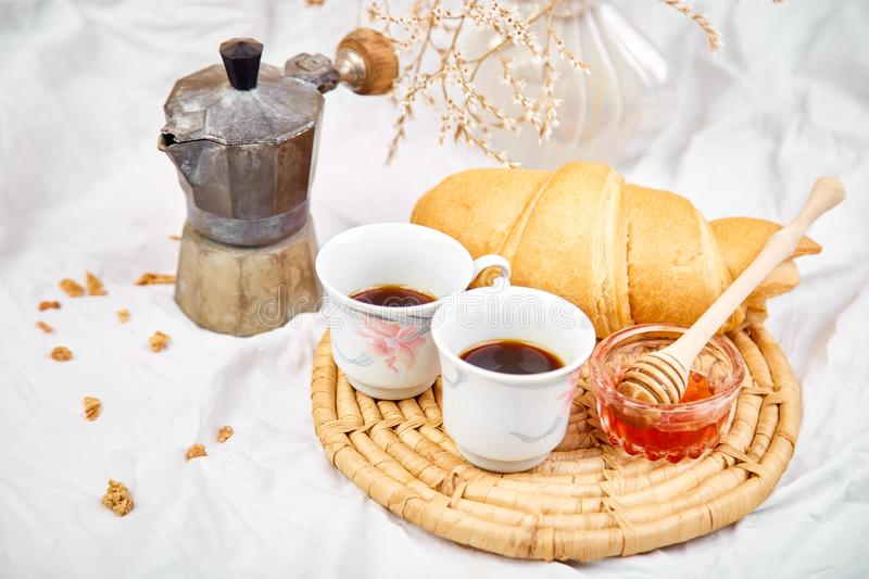 Good morning. Two cup of coffee with croissant and jam. Breakfast on white bed sheets from above. Top view. Flat lay. Copy space. Romantic breakfast stock photo