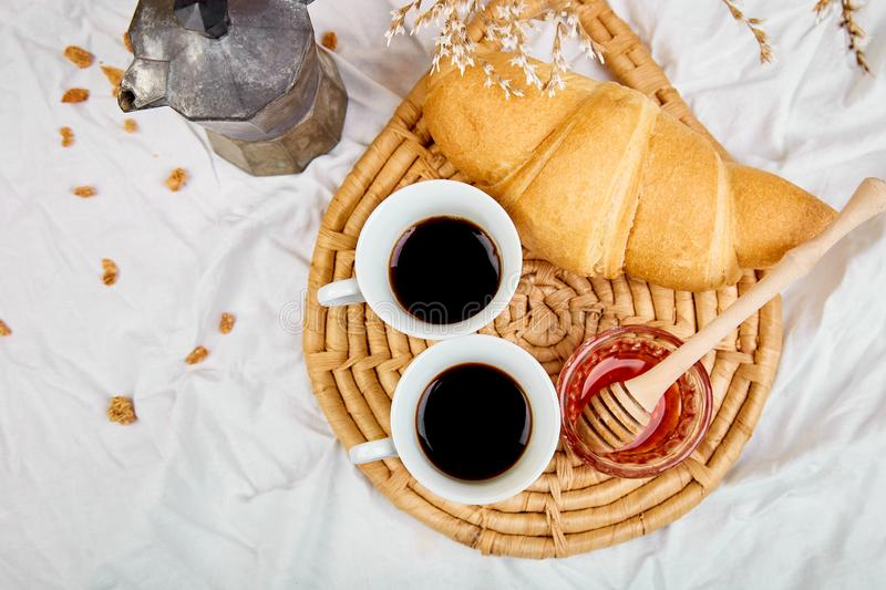 Good morning. Two cup of coffee with croissant and jam. Breakfast on white bed sheets from above. Top view. Flat lay. Copy space. Romantic breakfast royalty free stock images