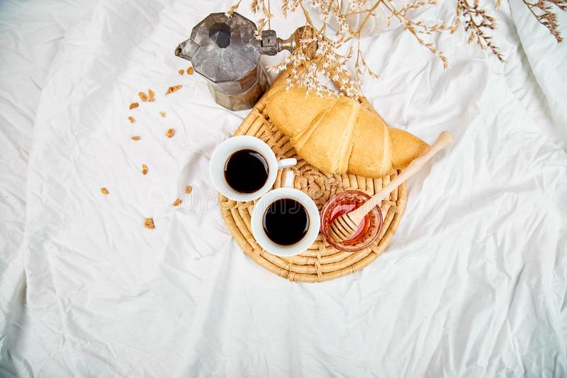 Good morning. Two cup of coffee with croissant and jam. Breakfast on white bed sheets from above. Top view. Flat lay. Copy space. Romantic breakfast royalty free stock photos