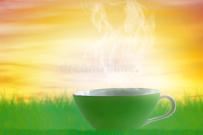Good Morning and Wake Up Concept. Cup of hot coffee on sunrise background royalty free stock photo