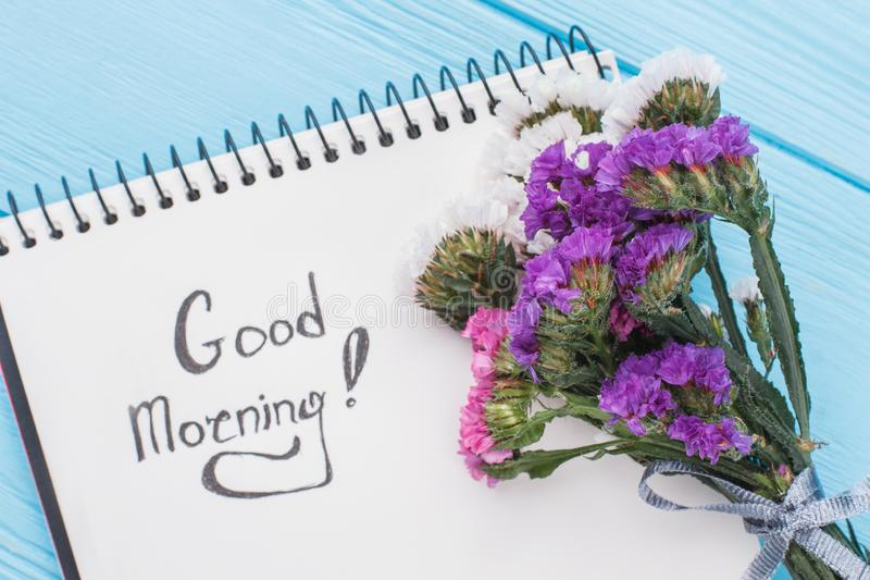 Good morning wish concept. Bouquet of statice limonium flowers and notepad with good morning wish. Blue background stock photography