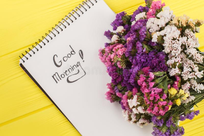 Good morning wish with limonium statice flowers. Yellow wooden table background stock photography