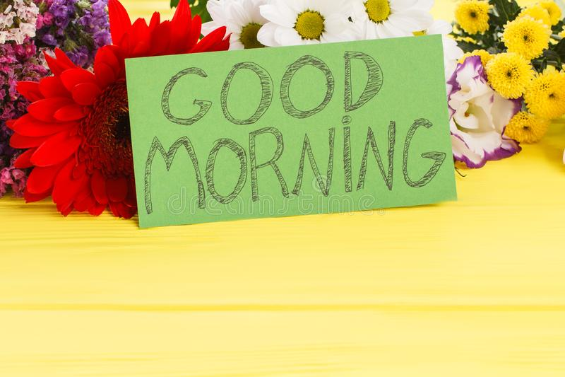 Good morning wish note and beautiful flowers. Close up. Yellow wooden desk background stock photo