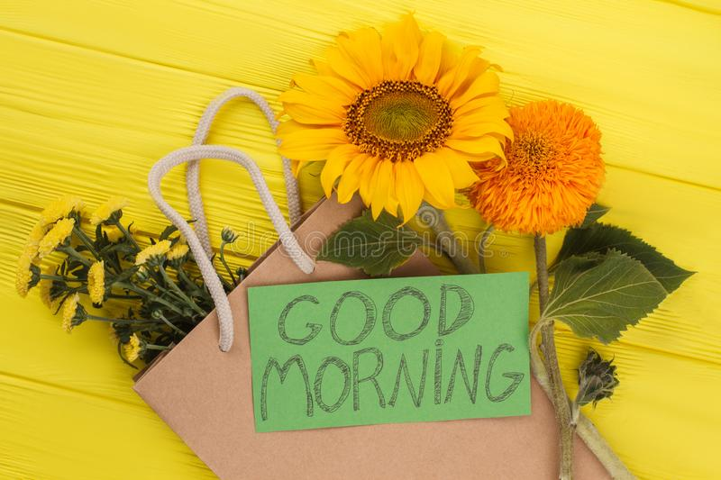 Good morning wish and young sunflowers. Yellow wooden background stock photo