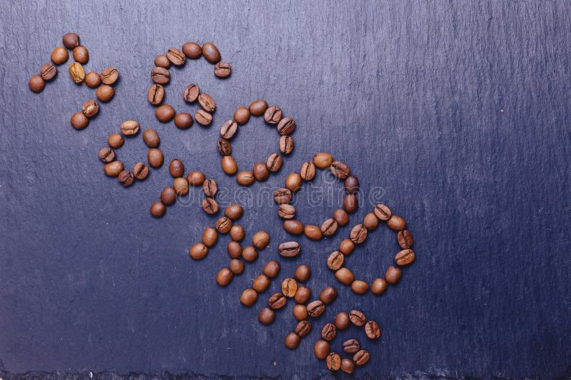 Good morning word by coffee beans on stone backdround. Good morning word by coffee beans on black stone backdround royalty free stock photography