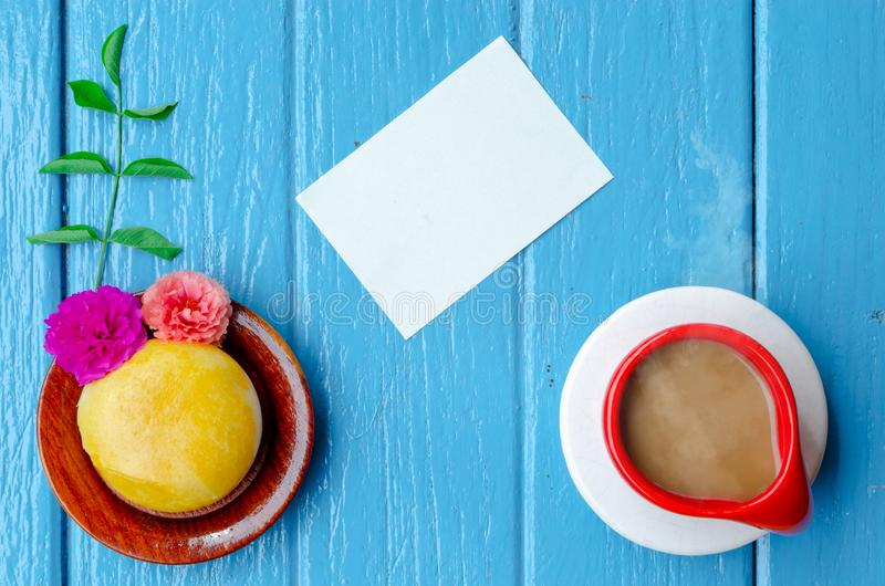 Good morning world. cup of coffee and yellow pie on blue background,top view ,empty space. royalty free stock image