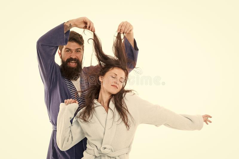 Good morning world. Go from flat to fluffy. happy bearded man play with hair of sleepy girl. family couple in robe. Love. Good morning world. Go from flat to stock photos