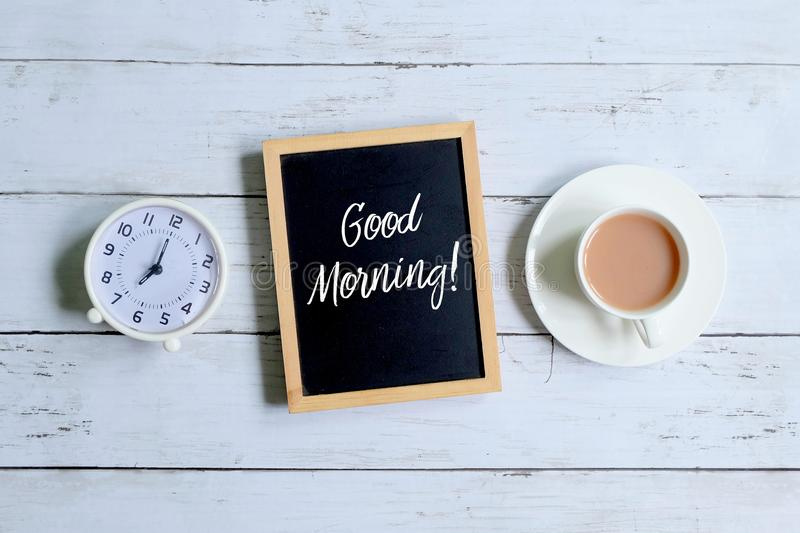 Good morning written on a blackboard with clock and coffee. Top view of table clock,a cup of coffee and blackboard written with `GOOD MORNING` on white wooden stock photography