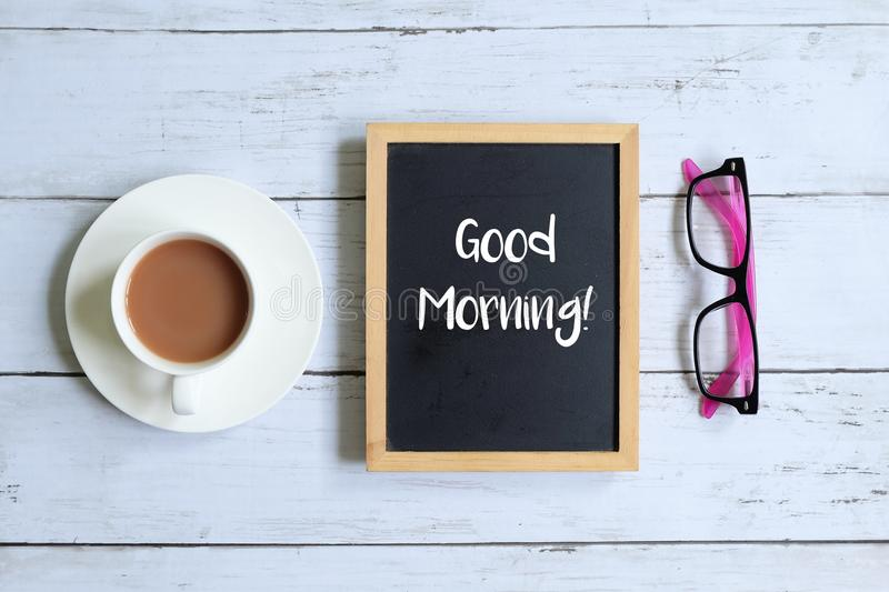 Good morning written on a blackboard. Top view of a cup of coffee, sunglasses and blackboard written with `GOOD MORNING` on white wooden background stock photos