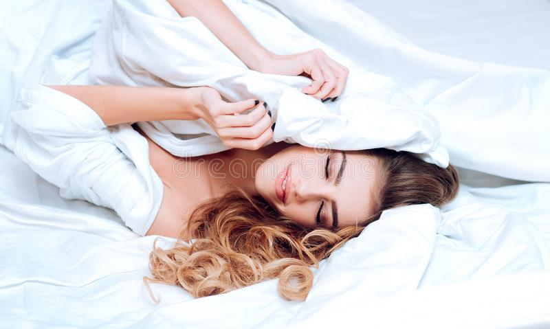 Good morning. Young woman holding in hands pillow in bed. Young woman sleeping in bed with pillows at home. Joyful woman stock photography