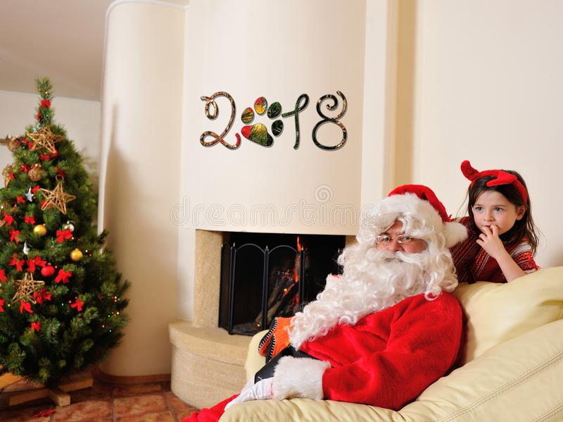 Good New Year spirit: tree, big gift bag, fireplace and decoration for year of the dog - Santa lay down on the floor and a cute d royalty free stock image