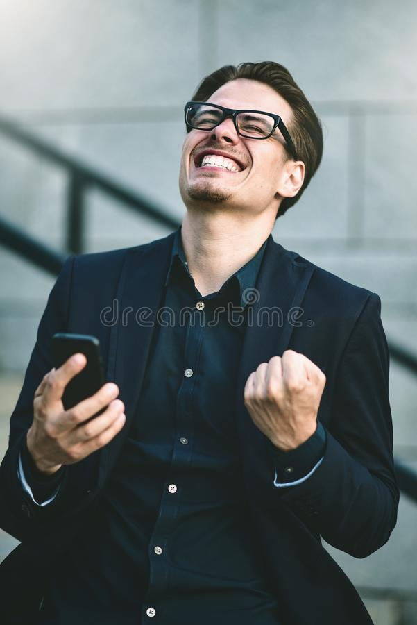 Good news Businessman got good news by phone standing at the street stock image