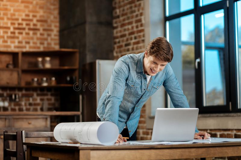 Happy man reading email from boss. Good news. Cheerful young engineer leaning on the table with his hands, having finished drawing the blueprint, reading an stock photos