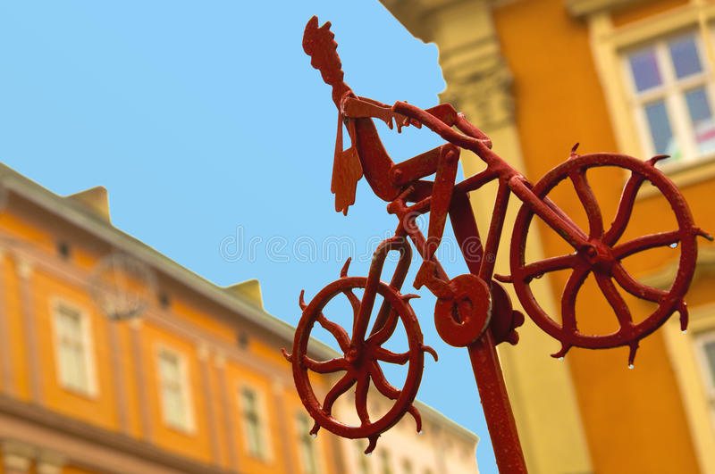 Good news, information, progress concept. Metal red figure of postman going up, riding bike and delivering mail and newspapers. A. Good news, information royalty free stock photography