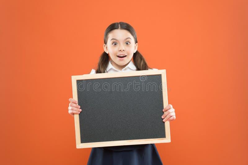 Good news for pupils community. Educational program. School schedule information. School girl cute pupil hold blackboard royalty free stock image