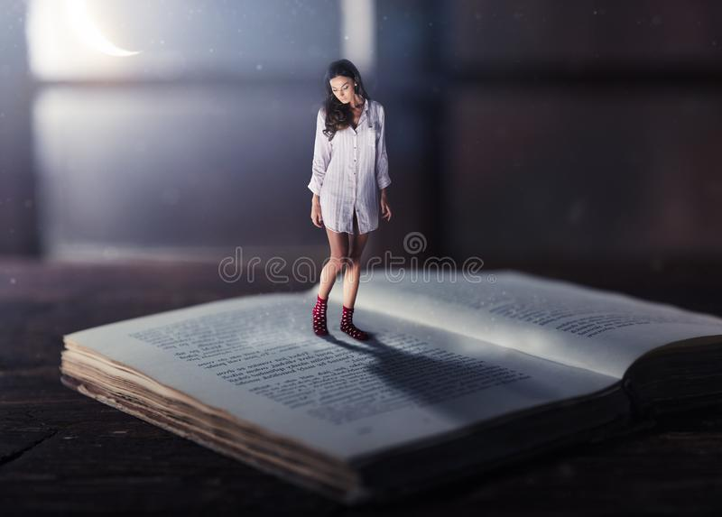 Good night concept with shrinked young woman. Reading book. Miniature unreal dreamy scene with moonlight royalty free stock image