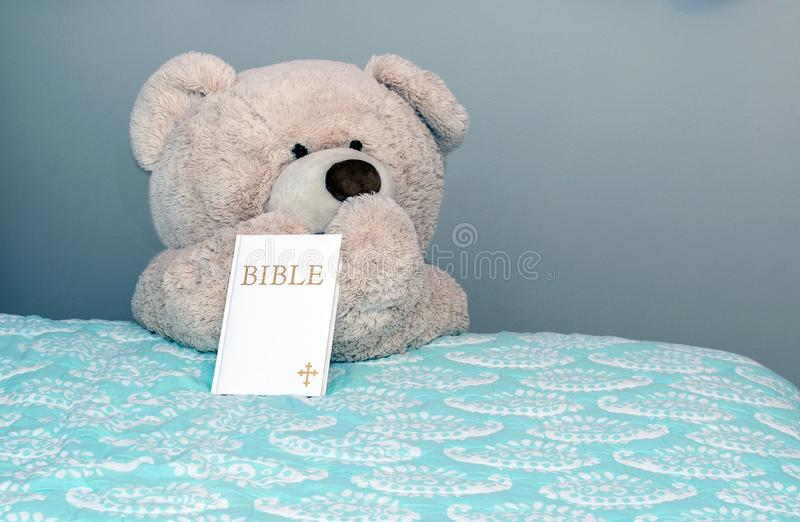 Good night teddy bear with prayers and bible. Good night teddy bear says prayers and has a bible by his side stock photography