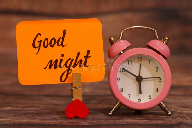 Good Night text attached with heart clip and alarm clock. royalty free stock image