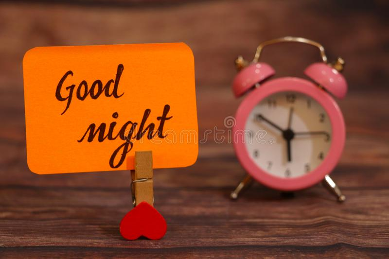 Good Night text attached with heart clip and alarm clock. royalty free stock photos
