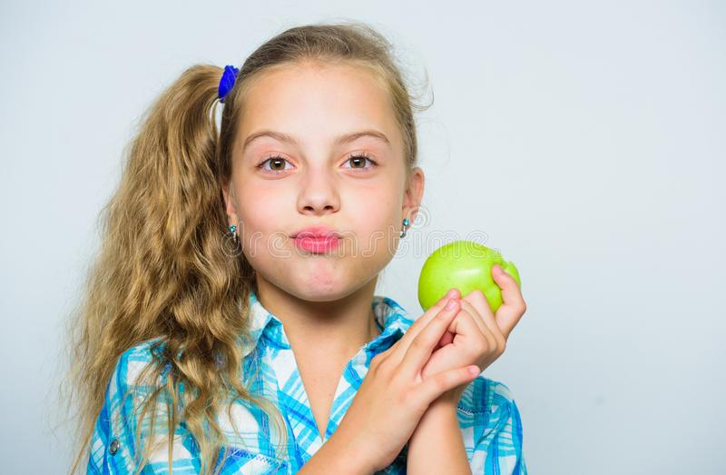 Good nutrition is essential to good health. Kid girl eat green apple fruit. Nutritional content of apple. Vitamin royalty free stock photo