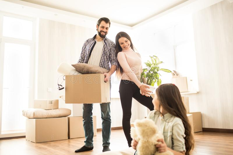 Good parents are standing close to each other and looking to their child. Man is holding a box with stuff. Woman has got. A plant in her hands. Their daughter royalty free stock photography
