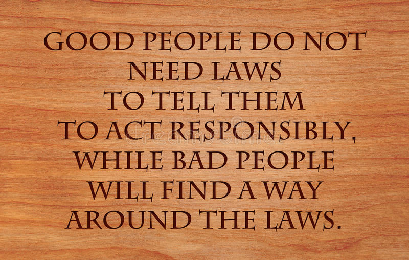 Good people do not need laws. To tell them to act responsibly, while bad people will find a way around the laws - quote by Plato on wooden red oak background royalty free stock image
