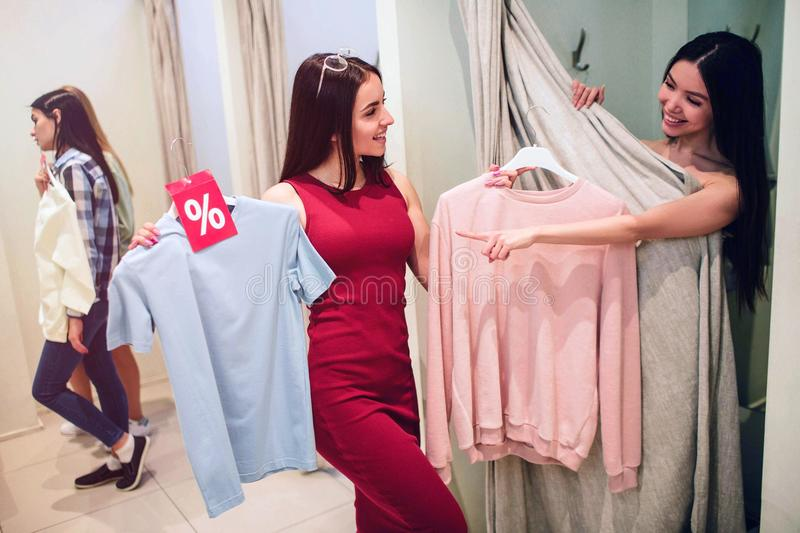 Good picture of asian girl trying on herself different clothes. Girl in dress gives her pink shirt but asian girl wants stock images