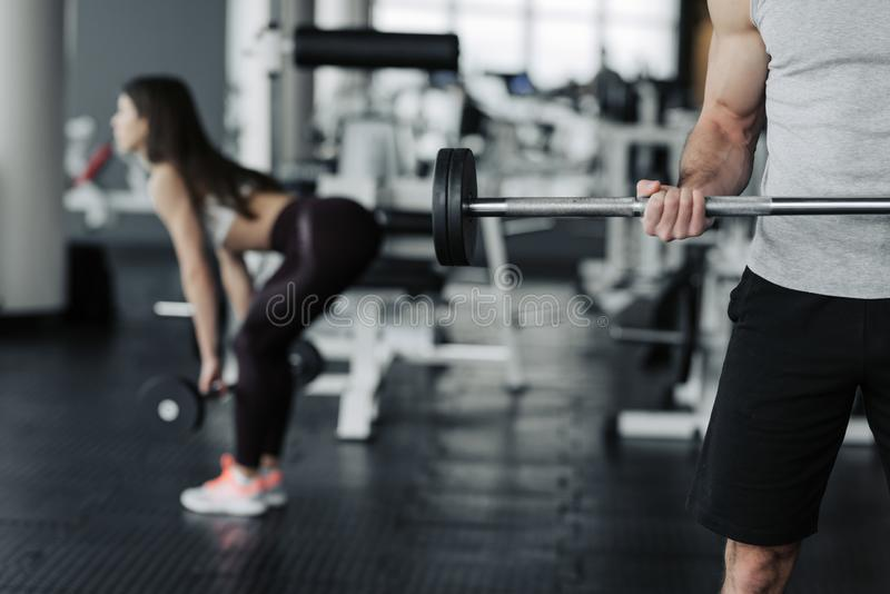 Good picture of boy and girl working out with dumbells in jym.  stock image