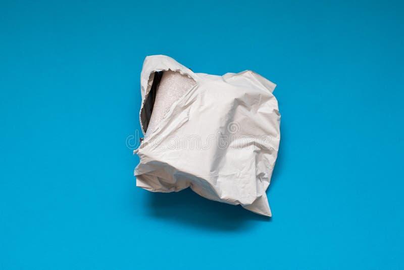 Damaged polyethylene envelope on blue background. Plastic Postal Mailing Bags royalty free stock photography