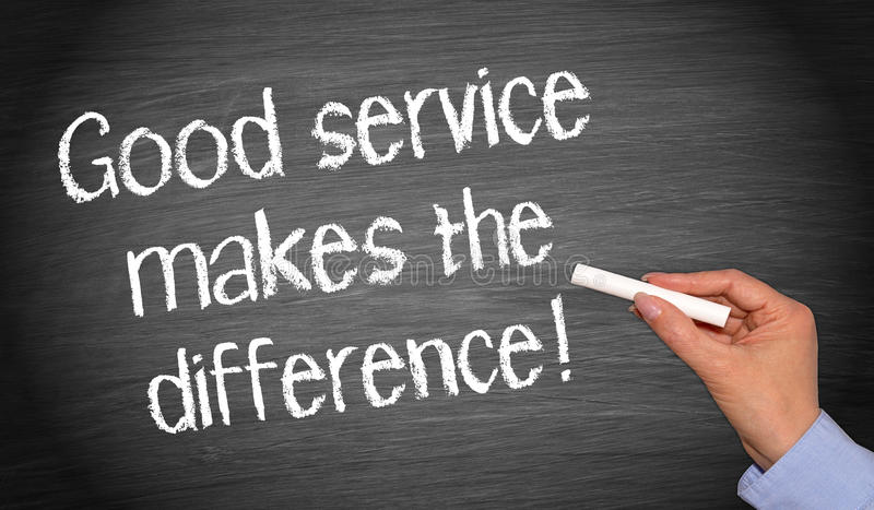 Good service makes the difference. Female hand with chalk writing text on blackboard stock photo