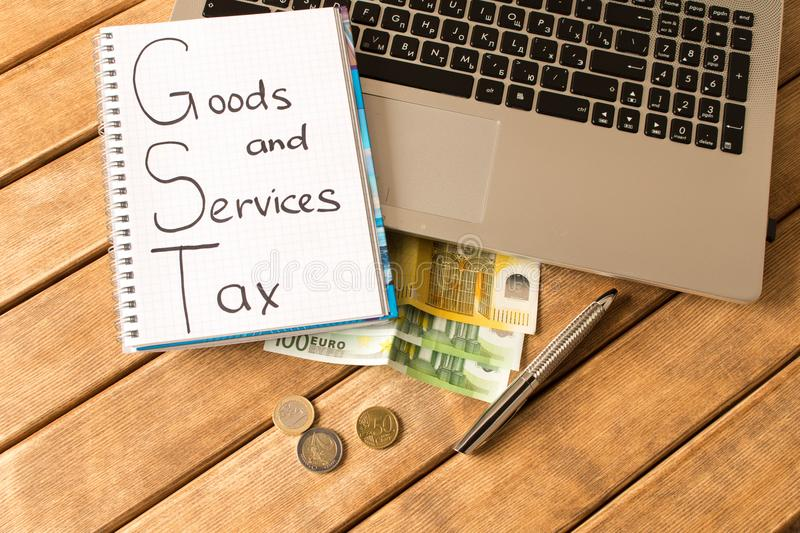 Good service and tax . Laptop, pen, coins, banknotes on wood ba. Ckground royalty free stock photos