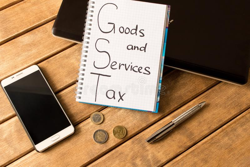 Good service and tax . Notebook, pen, coins, smart phone on woo stock photo