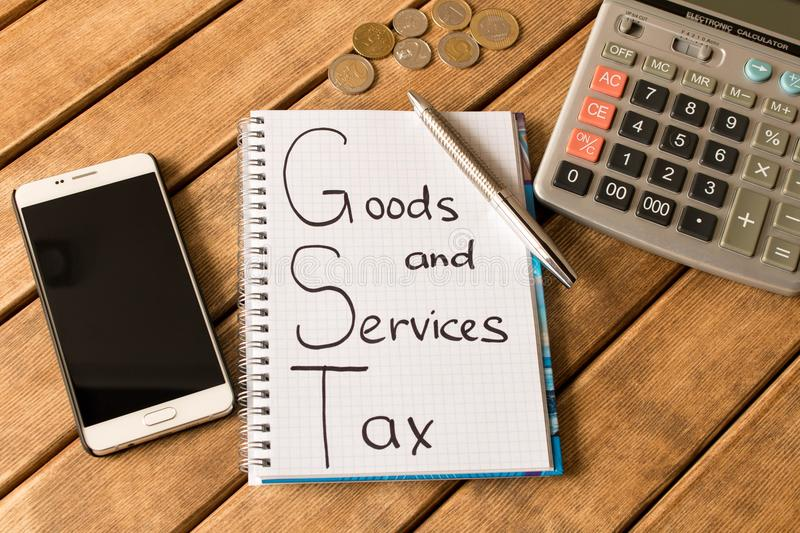 Good service and tax . Notepad, pen, coins, smart phone on wood stock photo