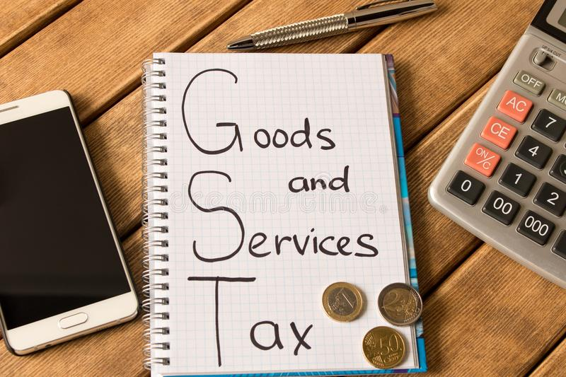Good service and tax . Notepad, pen, coins, smart phone on wood royalty free stock photo