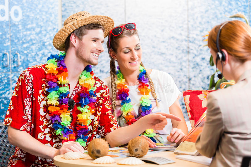 Good service in travel agency. Men and women booking a beach vacation stock image