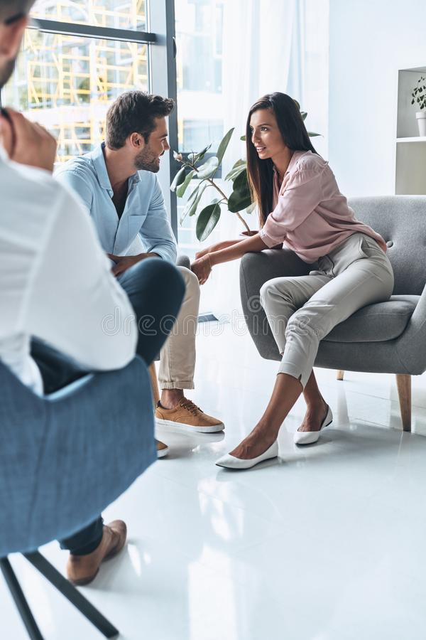 Good session. Young married couple talking and smiling while sitting on the therapy session with psychologist stock photos