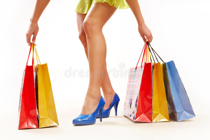 Good shopping. Legs of lady standing and holding colorful paper bags royalty free stock photo