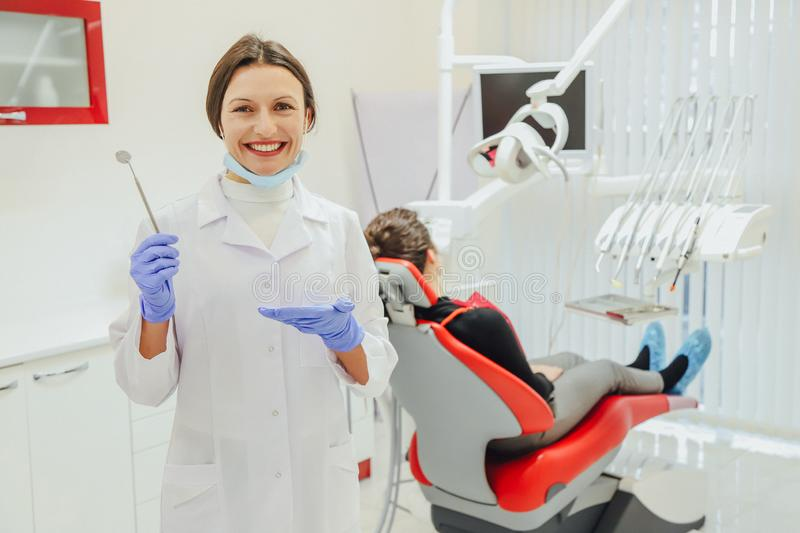 A good specialist. Portrait of a beautiful young woman dentist in a dressing gown and mask. Countering the clinic of stock image